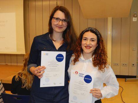 Zwei junge Frauen halten, mit einem strahlenden Lächeln, ihr Teilnahmezertifikat von