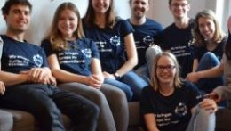 7 junge Menschen sitzten zusammen auf einer Couch. Si tragen alle das