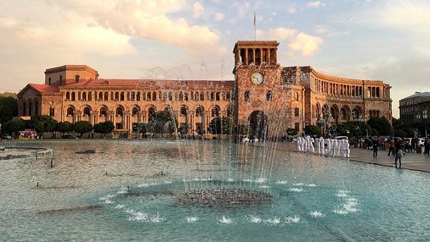 Im Vordergfund ist eine städtische Springbrunnenanlage zu sehen. Und im Hintergrund ein historisches Gebäude.