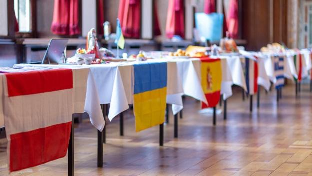 Aneinandergereihte Tische die mit einer weißen Tischdecke und einer europäischen Flagge geschmückt sind. Auf dem Tisch sind Ausstellungsstücke zu dem jeweiligen Land zu sehen.