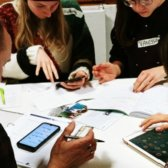 vier Menschen sitzen an einem Tisch. Vor ihnen haben sie Infomaterialien, Tablets, Handys und Kalender liegen.