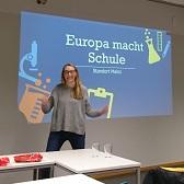 Eine junge Frau vom Standort-Team Mainz steht in einem Seminarraum und hält einen Vortrag zu dem Programm
