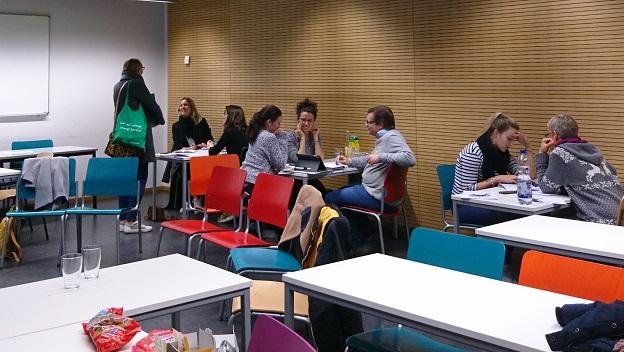 Gaststudierende und Lehrkräfte sitzen zusammen mit dem ehrenamtlichen Standort-Team an Tischen, um ihre Projektideen für