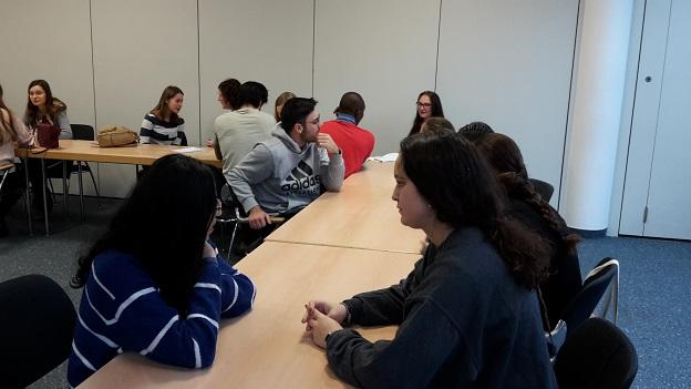Gaststudierende sitzen in Kleingruppen an Tischen und besprechen sich.