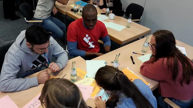 5 Gaststudierende sitzetn gemeinsam am Tisch und schreiben Stichpunkte auf bunte Moderationskarten