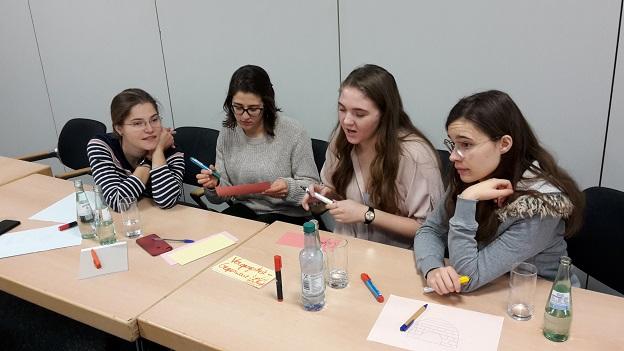 4 Gaststudierende sitzen an Tischen zusammen und schreiben Stichpunkte uf verschiedenfarbige Zetttel