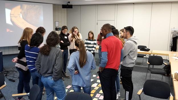 Eine Gruppe Gaststudierender steht im Kreis um verschieden beschriftete Moderationskarten