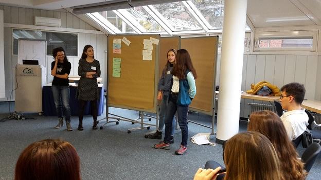vier Gaststudierende stellen an einer Pinnwand den anderen Teilnehmer/-innen der Schulung etwas vor