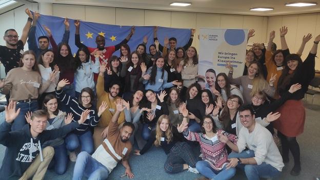 Alle Teilnehmerinnen und Teilnehmer der Schulung lachen in die Kamera und strecken freudig ihre Arme hoch. Die hinterste Reihe hält eine Europafahne hoch und im Hintergrund steht ein EmS-Rollbanner.