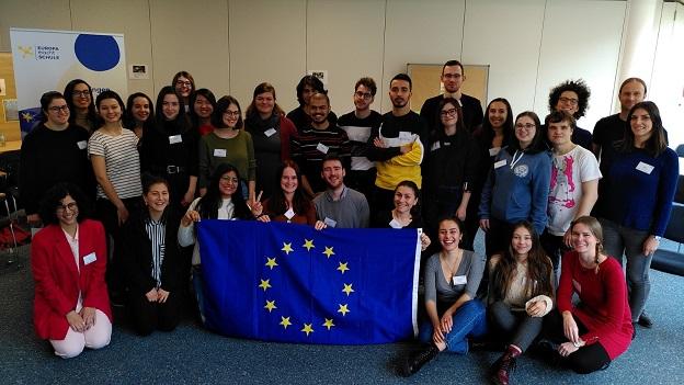Die Teilnehmer/-innen halten eine EU-Flagge in der Hand und lächeln in die Kamera