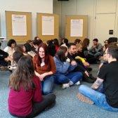 Teilnehmer/-innen sitzen auf dem Boden und tauschen sich aus