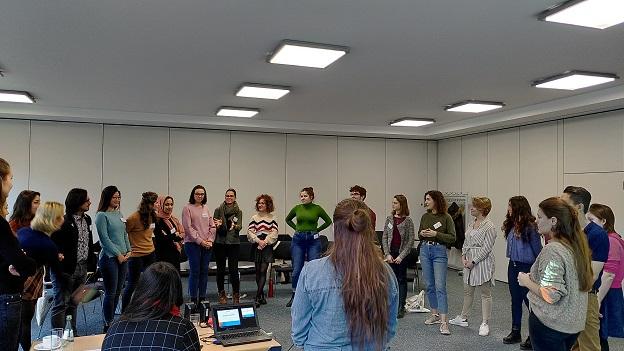 Teilnehmer/-innen stehen im Halbkreis und hören einenander zu