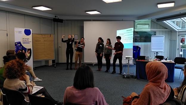 5 junge Leute stehen vor einer Power-Point-Präsentation und stellen etwas pantomimisch der Gruppe vor.
