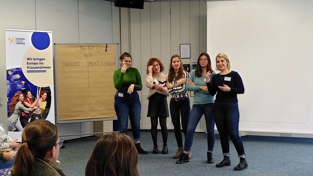 5 junge Frauen stehen vor dem Banner