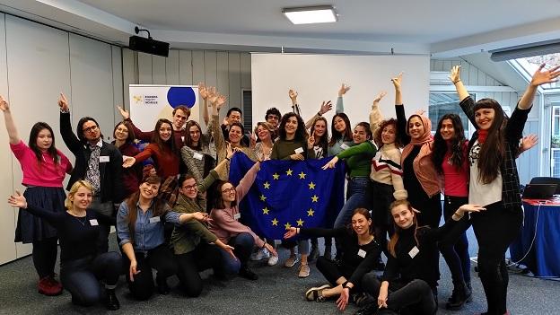 Alle Teilnehmer/-innen stehen im Halbkreis zusammen und halten die EU-Flagge in die Kamera