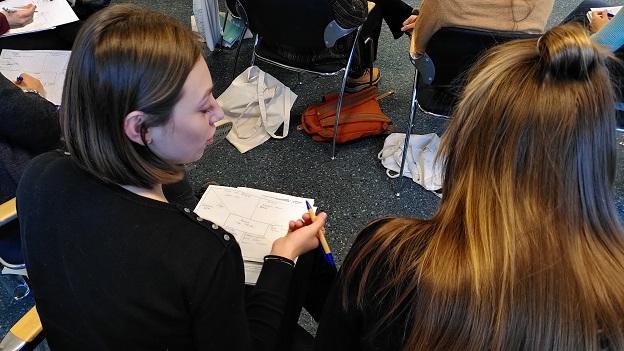 Zwei junge Frauen schreiben etwas auf ein Blatt Papier und besprechen sich dabei.
