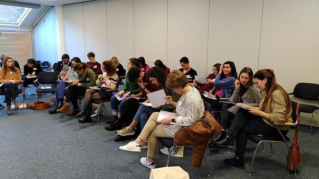 Die Teilnehmer/-innen sitzen im Stuhlhalbkreis und schreiben etwas auf ein Blatt Papier