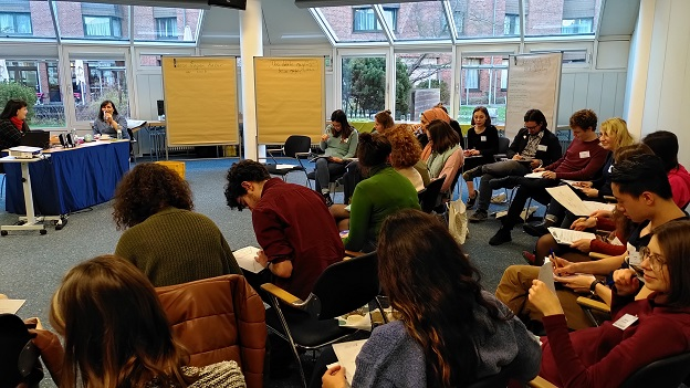 Alle Teilnehmer/-innen sitzen im zweireihigen Stuhlhalbkreis und schreiben etwas auf ein Blatt Papier. Die beiden Referentinnen sitzen vor ihnen an einem Tisch