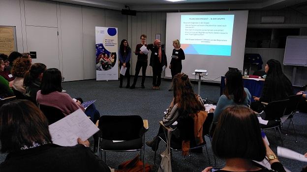 4 junge Gaststudierende stehen vor eine Power-Point-Präsentation und stellen den anderen Teilnehmer/-innen etwas vor.