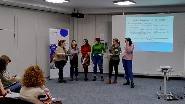 6 junge Frauen stehen vor der Power-Point-Präsentation mit der Überschrift