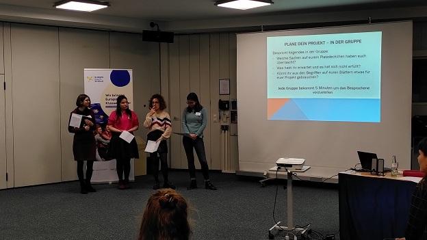 4 junge Frauen stehen vor der Power-Point-Präsentation mit der Überschrift