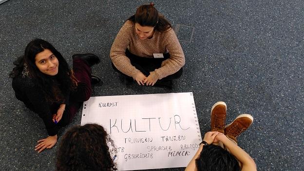 4 junge Studierende sitzen auf dem Boden um ein Plakat, zum Thema