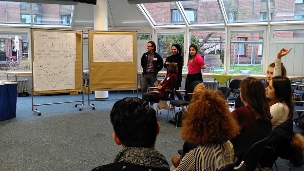 3 junge Gaststudierende stehen vor zwei Pinnwänden auf denen Plakate zum Thema
