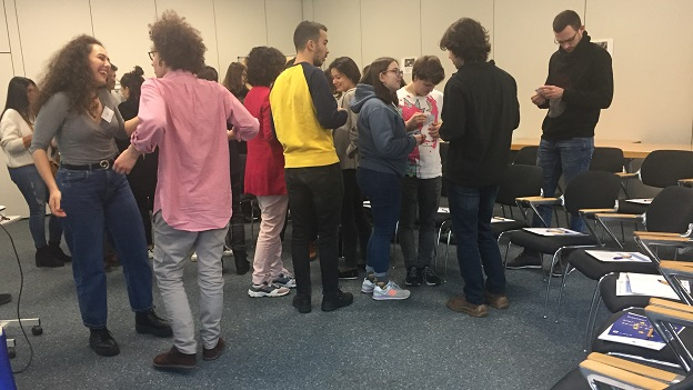 Die Teilnehmer/-innen stehen verteilt im Raum und tauschen sich angeregt aus