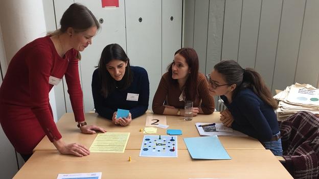 3 Teilnehmerinnen und eine Referentin sitzen am Tisch udn spielen das EmS-Mensch-ärgere-dich-nicht Spiel