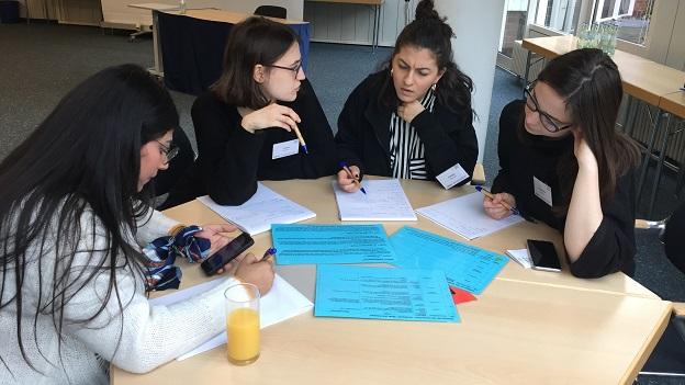 4 Teilnehmerinnen sitzen gemeinam an einem Tisch und lösen eine Aufgabe