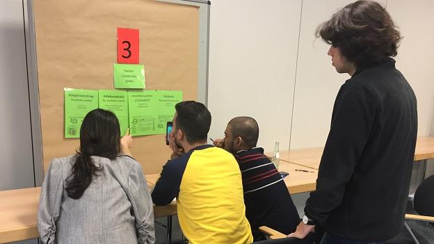 4 Teilnehmer/innen sitzen bzw. stehen vor einer Pinnwand, an welcher Aufgaben zu sehen sind und versuchen diese gemeinsam zu lösen