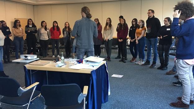 Alle Teilnehmer/-innen stehen im Halbkreis um den Referenten und hören ihm gespannt zu