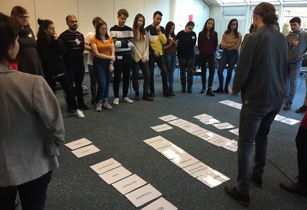 Die Teilnehmer/-innen stehen verteilt um, die am Boden liegende Moderationskarten und schauen diese an