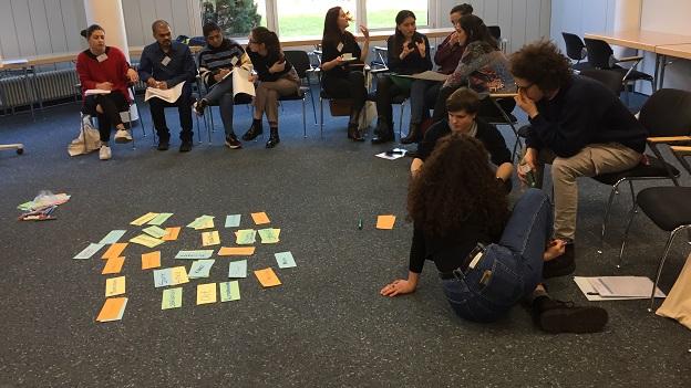 Die Teilnehmer/-innen sitzen im Halbstuhlkreis und beshcriften verschiedene Moderationskarten, welche anschließend in die Mitte gelegt werden