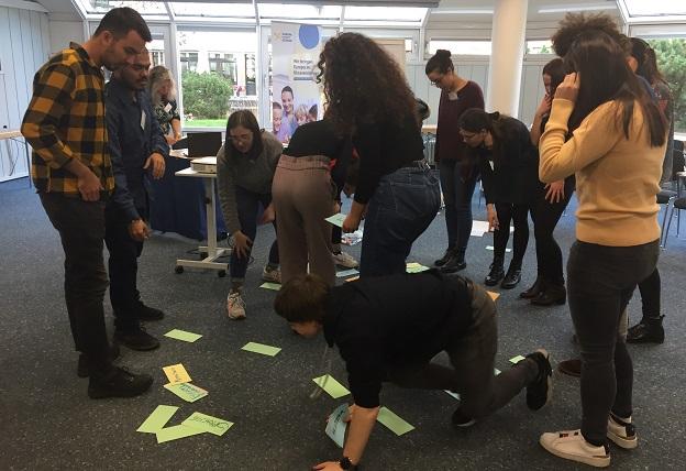 Die Teilnehmer/-innen stehen im Raum verteilt und ordnen gemeinsam Moderationskarten, welche verstreut auf dem Boden liegen