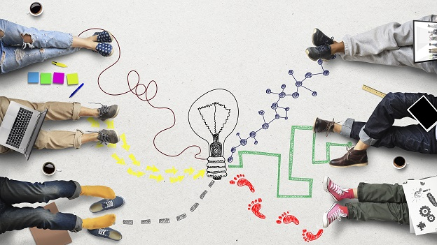 Auf dem Bild sieht man in der Mitte eine gezeichnete Glühbirne von der aus verschiedene Spuren zu jeweils einzelnen, am Rande sitzenden, Personen gehen.