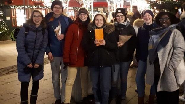 sieben junge Leute stehen aufgreiht auf dem Weihnachtsmarkt in Hamburg und lächeln in die Kamera.
