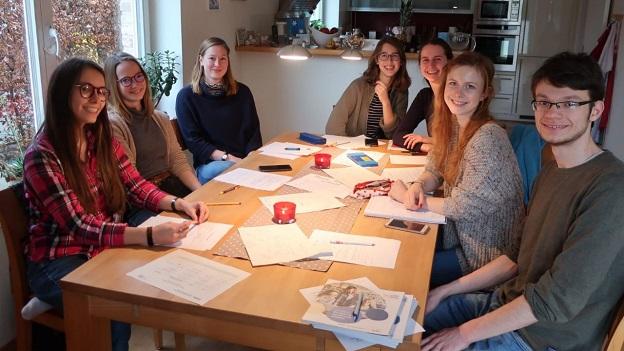 7 junge Menschen sitzen an einem Tisch, auf welchem Zettel und Stifte liegen, und lächeln in die Kamera