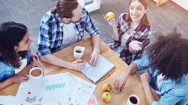 3 junge Frauen und 1 junger Mann sitzen um einen Holztisch, auf den man von oben schaut. Eine Frau hält einen Apfel in der Hand und macht eine fragende Geste, die anderen 3 Personen schauen sie an. Auf dem Tisch liegen Arbeitsmaterialien.
