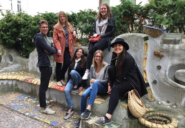 6 Vorstandmitglieder des Vereins Europa macht Schule e.V.  sitzen bzw. stehen auf einer Bank und blicken in die Kamera