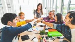 Eine Gruppe junger Personen verschiedener ethnischer Herkunft sitzen an einem Tisch und strecken ihre Fäuste einander zu. Auf dem Tisch liegen verschiedenste Büroartikel und Unterlagen. Sie befinden sich in einem hell-beleuchteten Büro mit großen Fenstern.