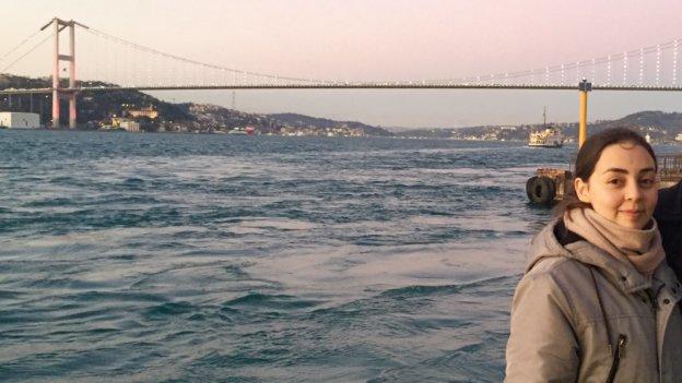 Frau Apkinar steht im Vordergrund. Im Hintergrund ist der Bosporus und eine Brücke zu sehen.