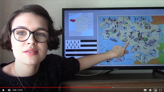 Eine junge Frau schaut in die Kamera und zeigt mit dem Finger auf eine Region in Frankreich