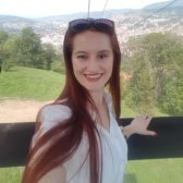 Frau Imamovic steht im Vordergrund. Im Hintergrund ist Sarajevo umgeben von einer grünen Landschaft zu sehen sowie die Trebevic Seilbahn.