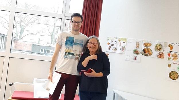 Ein junger Mann und eine Frau stehen in einem Klassenzimmer und lächeln in die Kamera