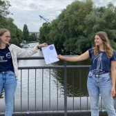 Die Zertifikatübergabe vom Standort-Team an eine Gaststudierende auf einer Brücke in Hamburg