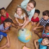 Eine Schulklasse inkl. Lehrerin stehen im Kreis um einen Globus.