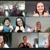 Screenshot einer virtuellen Videokonferenz, bei der alle die Daumen hochheben und in die Kamera lächeln