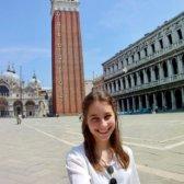 Frau Bonato steht im Vordergrund. Hinter ihr ist ein großer Platz mit Gebäuden und einem Turm zu sehen.