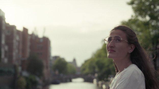 Frau Sanuy Suz steht rechts im Vordergrund. Im Hintergrund ist verschwommen eine Stadt und ein Fluß mit Bäumen und Häusern an der Seite zu erkennen.